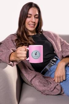 ソファに座ってマグカップを持つスマイリー女性