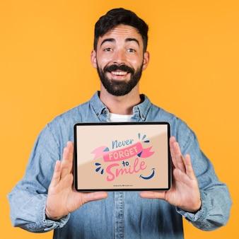モックアップタブレットを提示するひげを生やした男の笑みを浮かべてください。