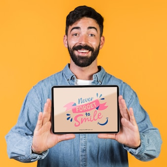 Smiling bearded man presenting a tablet mock up