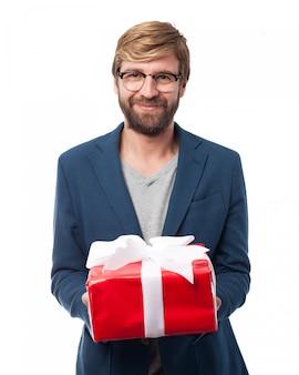 Улыбаясь исполнительной держит подарок на день рождения
