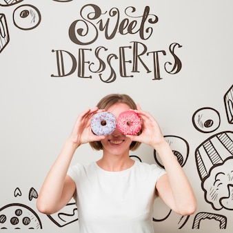 Smiling woman looking through donuts
