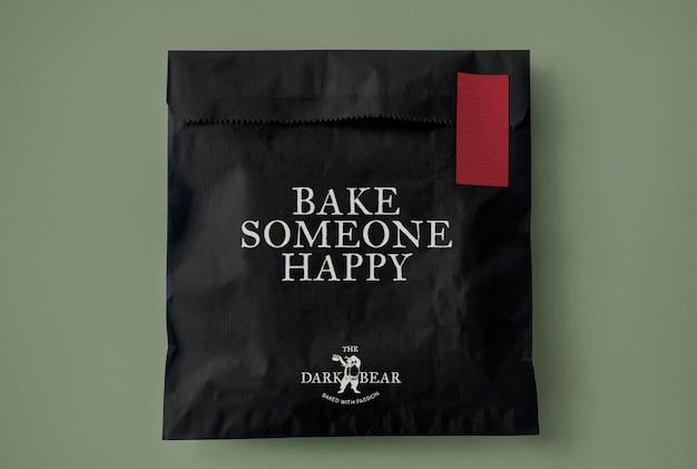 Psd макет бумажного пакета с закусками в классическом черно-красном дизайне фирменного стиля упаковки