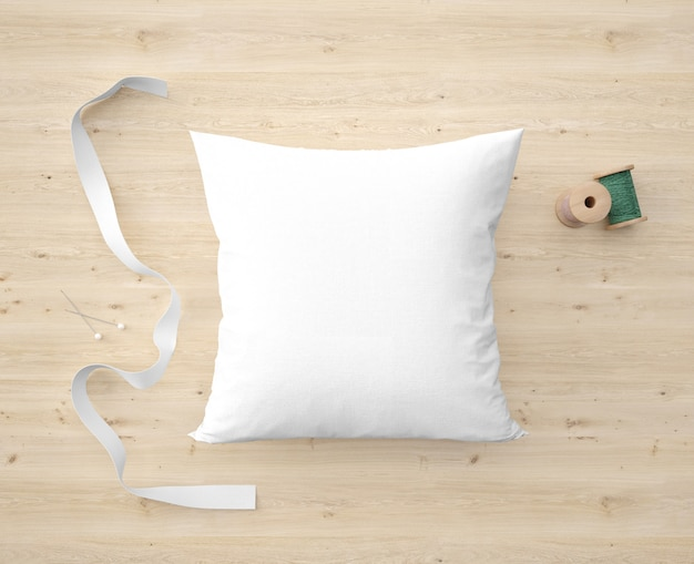 Soft white pillow, ribbon and green thread
