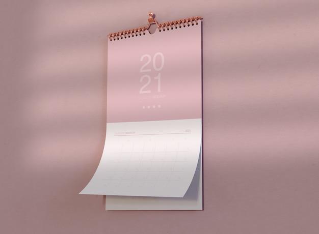 Мокап спирального календаря, висящий на стене