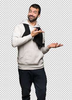 Sport man extending hands to the side for inviting to come