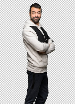 Sport man keeping the arms crossed in lateral position while smiling