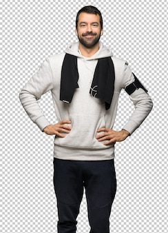Sport man posing with arms at hip and laughing looking to the front