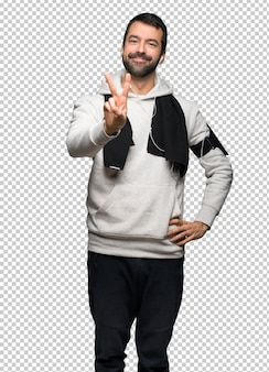 Sport man smiling and showing victory sign