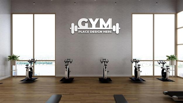 Макет спортивного логотипа в фитнес-зале с белой стеной