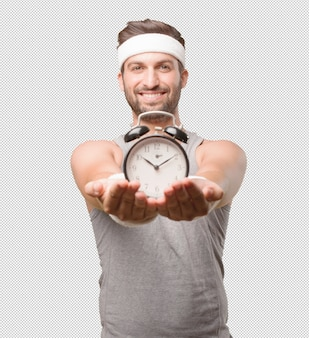 Sporty man with alarm clock