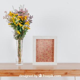 Spring mockup with vertical frame and vase of flowers over table