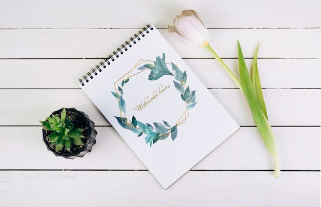 Spring notebook mockup with decorative plant in top view