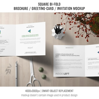 Square bi-fold brochure or greeting card mockup on creative workspace