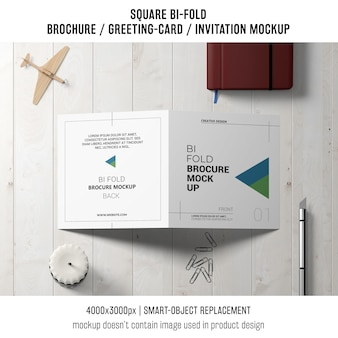 Square bi-fold brochure or greeting card mockup with decoration on tabletop