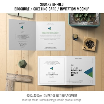 Square bi-fold brochure or greeting card mockup on wooden table
