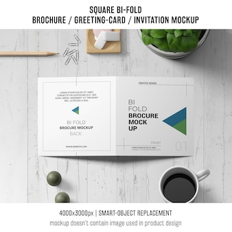Square bi-fold brochure or greeting card mockup on wooden workspace