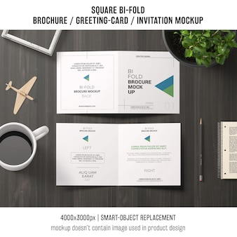 Square bi-fold brochure or greeting card mockup on workspace