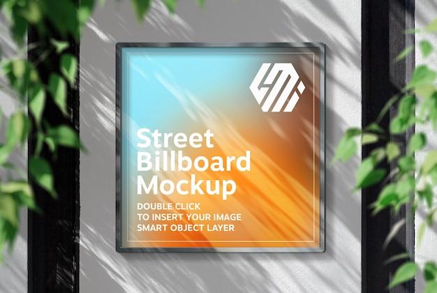 Квадратный рекламный щит, висящий на солнечной стене, макет