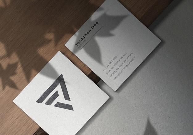 Square business card mockup design on wooden board