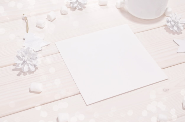 Square card mockup with white decorations on wood table
