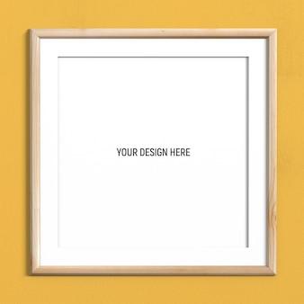 Square light wood frame mockup on yellow textured wall