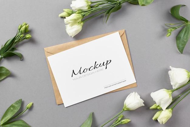 회색 배경에 흰색 eustoma 꽃과 고정 카드 모형