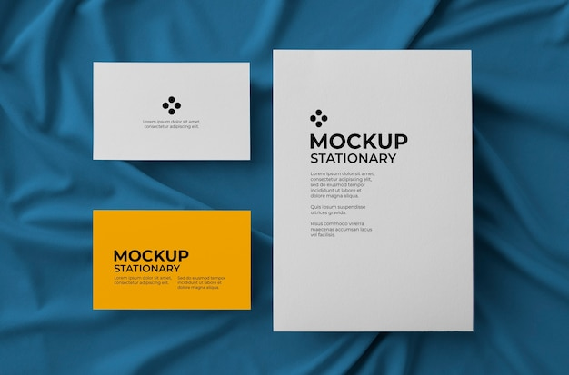 Stationary with big card and two bussiness cards over fabric background mockup