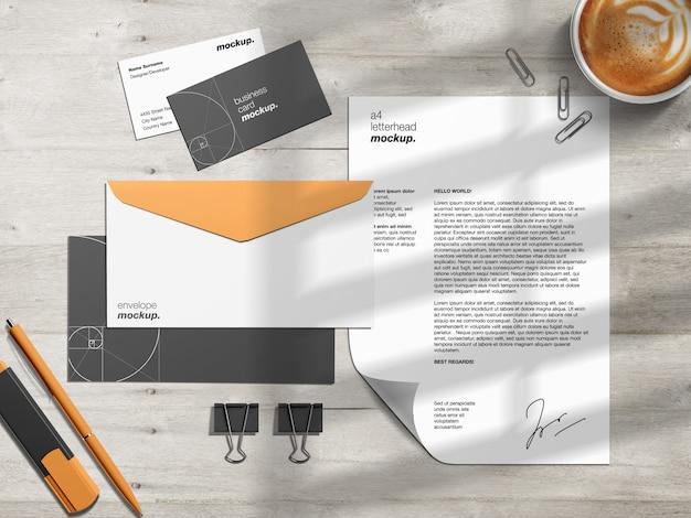 Шаблон макета фирменного стиля для канцелярских товаров и создатель сцены с фирменным бланком, визитками и конвертами на рабочем столе