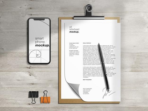 ペンと紙の目隠しと文房具のクリップボードのレターヘッドとスマートフォンのモックアップテンプレート