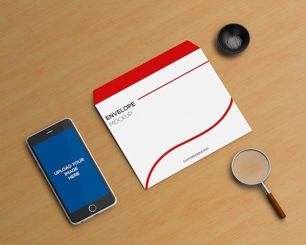 Concetto di cancelleria con busta e smartphone mockup