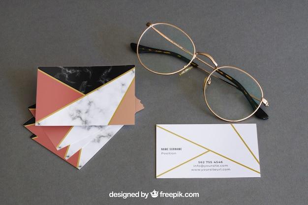 Mockup di cancelleria con occhiali e biglietti da visita