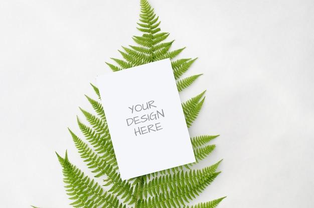 ミニマリストスタイルのホワイトスペースに緑のシダを持つ文房具モックアップ