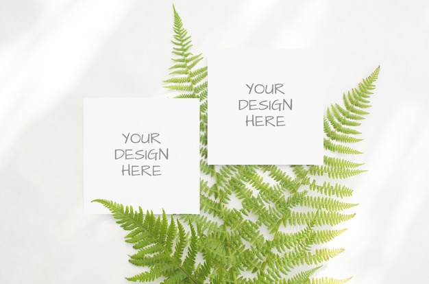 Stationery mockup with green ferns on a white space in a minimalist style