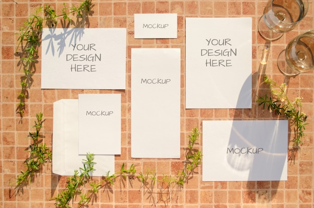Stationery mockup with herbs, glasses of wine and falling shadows on orange