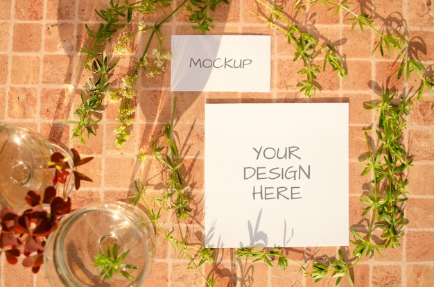 Stationery mockup with herbs, glasses of wine and falling shadows on peach orange