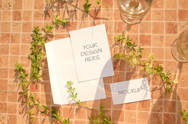 Stationery mockup with herbs, glasses of wine and falling shadows on a peach orange