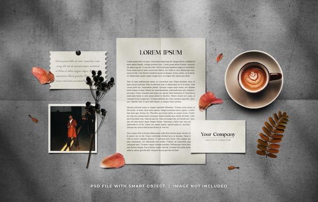 一杯のコーヒーと乾燥した植物の文房具セットのモックアップ