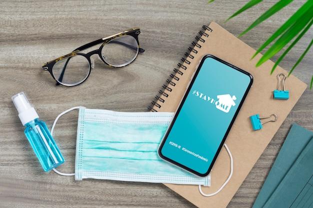 Оставайтесь дома хэштегом, концепция кампании профилактики пандемического коронавируса. макет мобильного телефона с лицевыми масками и alcohol mini hand sanitizer spray на офисном столе.