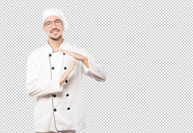 그의 손으로 시간 초과 제스처를 만드는 젊은 요리사를 강조