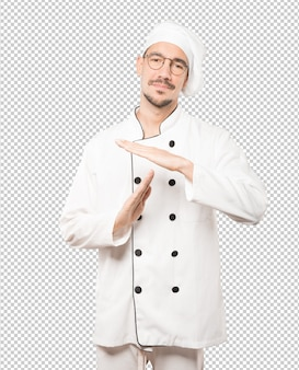 Stressed young chef making a time out gesture with his hands