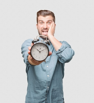Stressed young man holding alarm clock