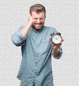 알람 시계를 들고 젊은 남자를 강조