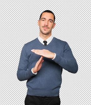 彼の手でタイムアウトジェスチャーを作るストレスの若い男
