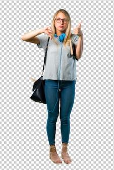 Девушка студента с стеклами делая хороший плохой знак. нерешительный человек между да или нет