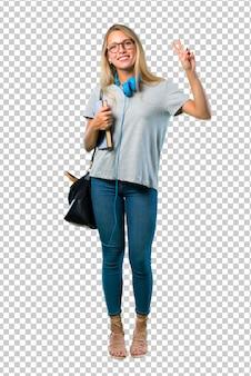 안경 웃 고 양손으로 쾌활 한 얼굴로 승리 기호를 보여주는 학생 소녀