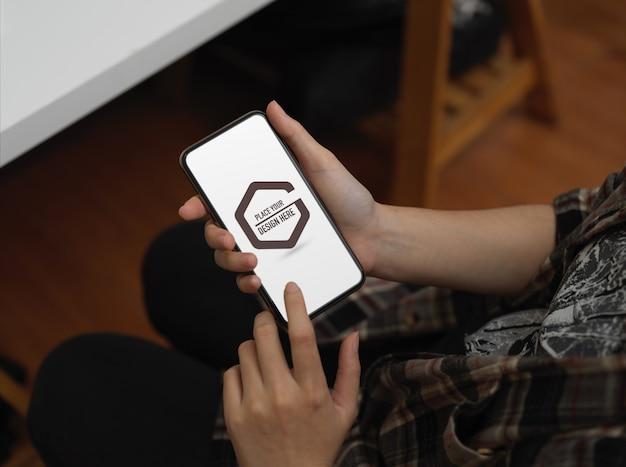 Студент руки с помощью макета смартфона в офисе