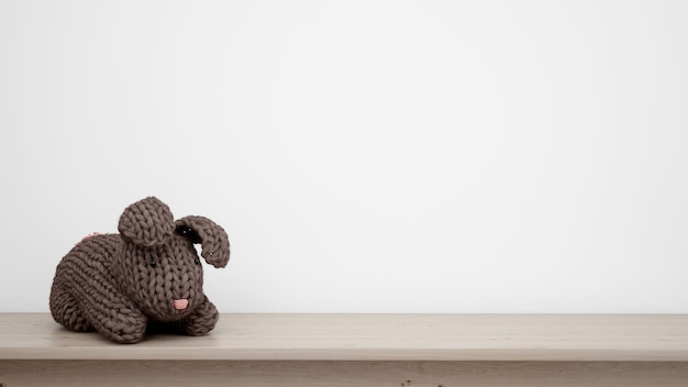 Stuffed bunny over white wall with copyspace