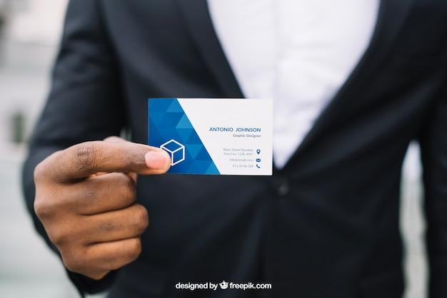 Стильный бизнесмен, держащий визитную карточку макета