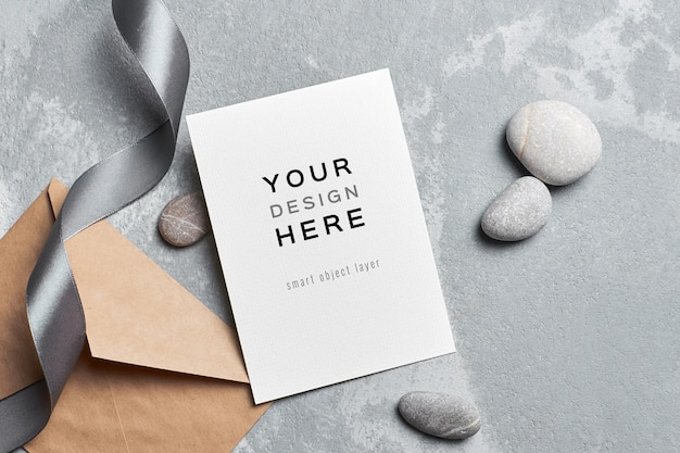 Stylish greeting card mockup with envelope and stones