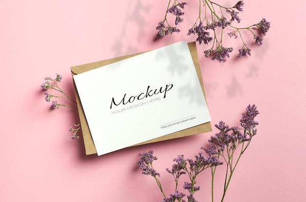 Limonium 꽃과 그림자가있는 핑크색 종이에 세련된 고정 카드 모형